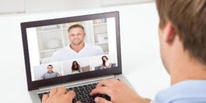 The view from behind, on a man taking part in a video conference