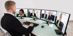 The man takes part in a video conference with 5 people, each of them on a separate monitor