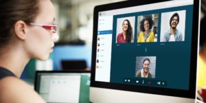 A young woman with glasses is talking to 4 people on a video conference